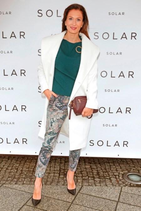 a6aa8142816cf1 Anita Sokołowska w cielonej bluzce, białym płaszczu i obcisłych spodniach  we wzory.