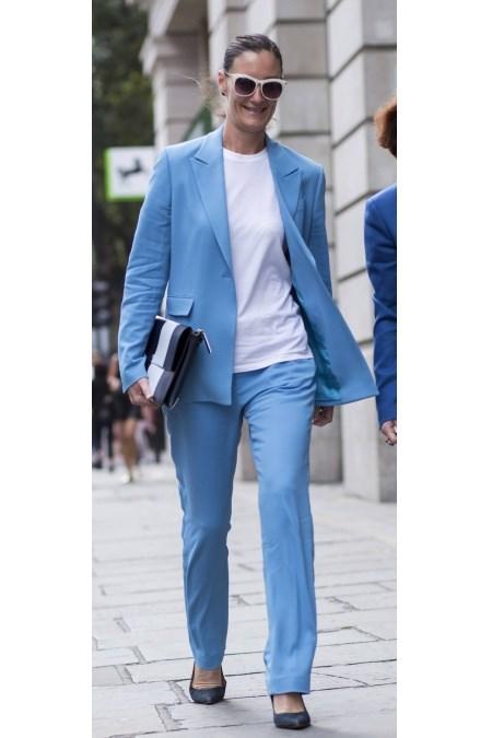 8d935d35ec Młoda kobieta w błękitnym garniturze składającym się z marynarki i  eleganckich spodni.